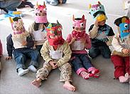 子供たちが手作りのお面をかぶって座っている写真
